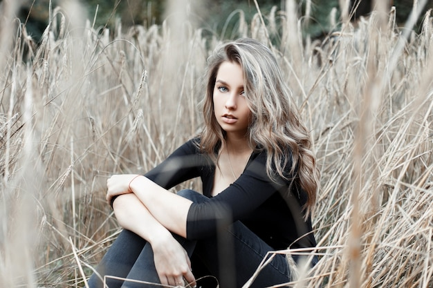 Piękna młoda ładna kobieta blondynka w stylowe dżinsy w modnej czarnej koszuli odpoczywa siedząc na polu wśród suchej trawy jesienią