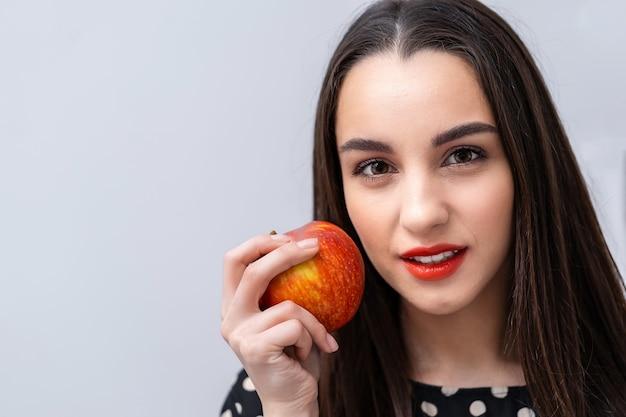 Piękna młoda ładna kobieta, modelka, dziewczyna z czerwonymi ustami. dziewczyna je jabłko, uśmiechając się. zbliżenie