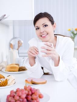 Piękna młoda ładna kobieta śniadanie w kuchni