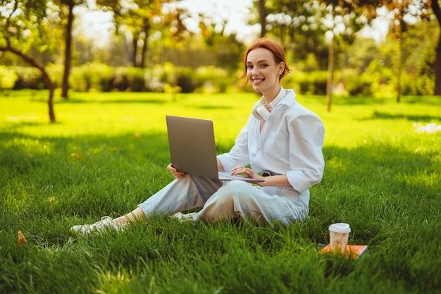 Piękna młoda ładna ruda kobieta w parku na świeżym powietrzu przy użyciu laptopa do nauki lub pracy online...