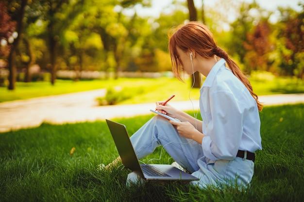 Piękna młoda ładna ruda kobieta w parku na świeżym powietrzu przy użyciu laptopa do nauki lub pracy przewodowej ...