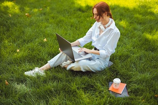 Piękna młoda ładna ruda kobieta w parku na zewnątrz przy użyciu komputera przenośnego do nauki lub pracy