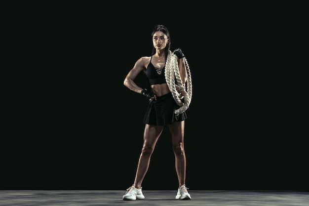 Piękna młoda lekkoatletka ćwicząca na czarnym tle studio portret pełnej długości