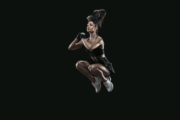 Piękna młoda lekkoatletka ćwicząca na czarnym tle