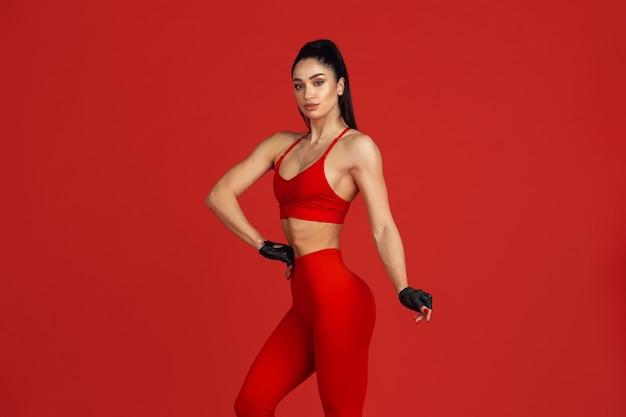 Piękna młoda lekkoatletka ćwicząca na czerwonej ścianie studia