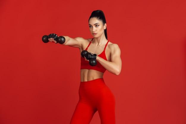 Piękna młoda lekkoatletka ćwicząca na czerwono