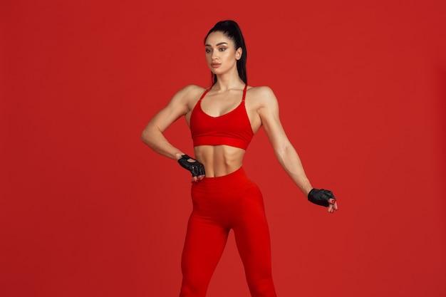 Piękna młoda lekkoatletka ćwicząca na monochromatycznym portrecie na czerwonej ścianie