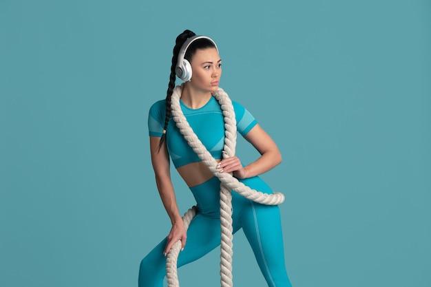 Piękna młoda lekkoatletka praktykujących, monochromatyczny niebieski portret. sportowy dopasowany model brunetka z linami i słuchawkami. koncepcja budowy ciała, zdrowego stylu życia, piękna i działania.