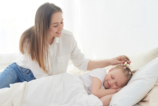 Piękna młoda mama budzi rano swoją nastoletnią córeczkę. czułość i troska. matczyna miłość.