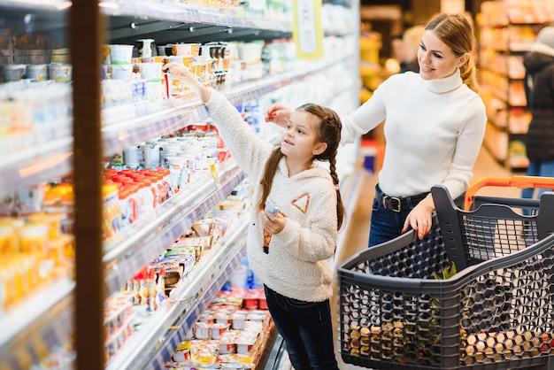 Piękna młoda mama i jej córeczka uśmiecha się i kupuje jedzenie