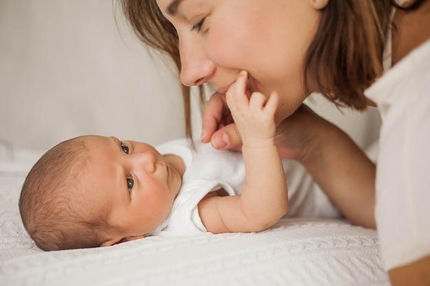 Piękna młoda matka bawi się z dzieckiem w łóżku. macierzyństwo.