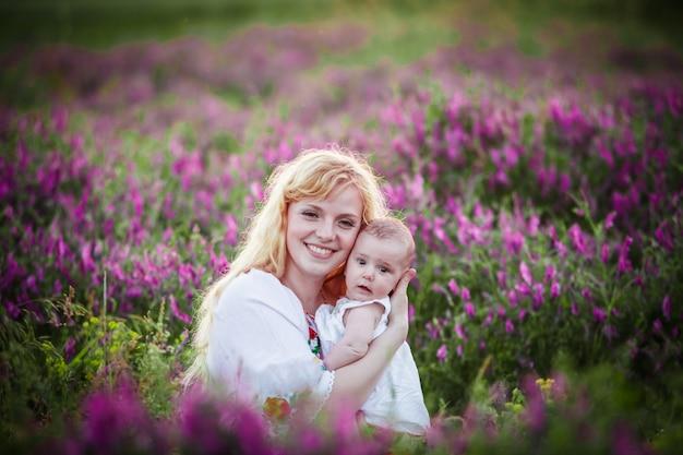 Piękna młoda matka czule trzymająca swoje małe urocze dziecko o zachodzie słońca na polu