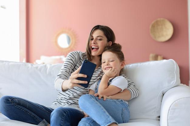 Piękna młoda matka i jej córeczka robienia selfie ze smartfonem w domu na kanapie.