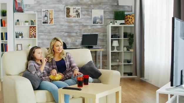 Piękna młoda matka i jej córka ogląda telewizję, siedząc na kanapie w salonie.