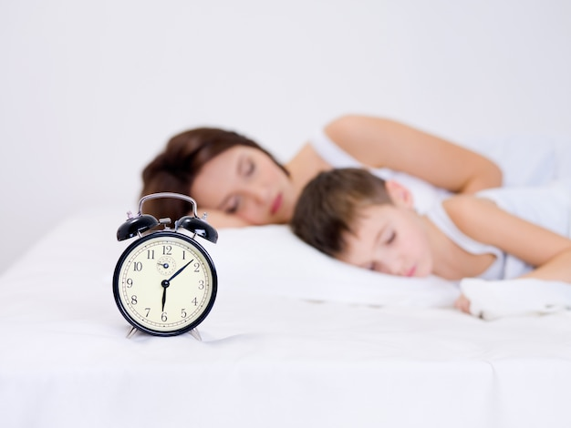 Piękna młoda matka i jej syn w wieku przedszkolnym śpi z budzikiem