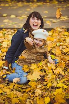Piękna młoda matka i jej szczęśliwa córka bawią się jesienią w lesie. spacery z dziećmi po jesiennym parku. rodzina świetnie spędzająca czas bawiąc się razem z opadłymi liśćmi.