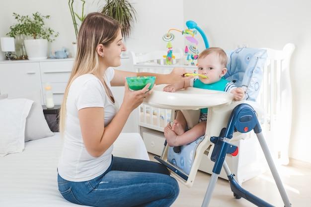 Piękna młoda matka karmi swojego chłopca w krzesełku z owsianką
