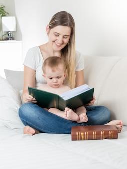 Piękna młoda matka pokazuje zdjęcia swojemu synkowi w dużym rodzinnym albumie