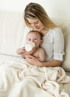 Piękna młoda matka siedzi na łóżku i karmi swoje dziecko butelką