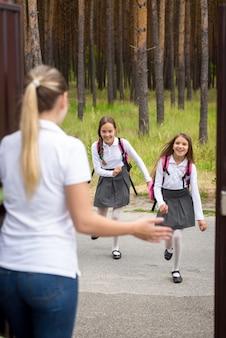 Piękna młoda matka spotyka córki po szkole w drzwiach