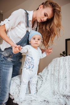 Piękna młoda matka stoi i opiekuje się swoim małym synkiem w domu