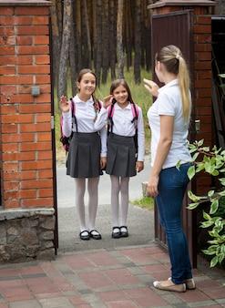 Piękna młoda matka stoi na podwórku i macha do córek idących do szkoły