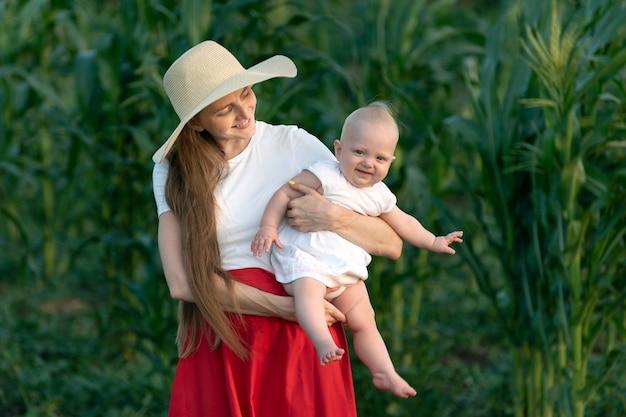 Piękna młoda matka trzyma uśmiechnięte dziecko na tle zieleni. szczęśliwe macierzyństwo. święta rodzinne.