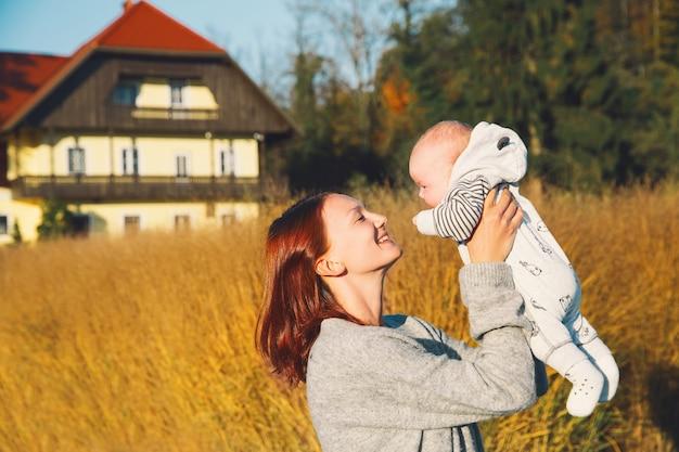 Piękna młoda matka trzyma w ramionach swoje dziecko w jesiennym parku. szczęśliwa mama z dzieckiem na naturze.