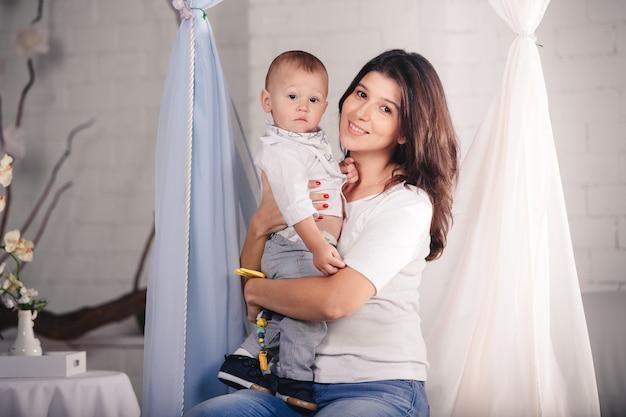 Piękna młoda matka, trzymając chłopca w ramionach w domu w jasnym, nowoczesnym wnętrzu w pomieszczeniu. kobieta o ciemnych włosach z uroczym dzieckiem, patrząc na kamery i uśmiechnięty. dzień matki.
