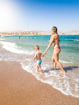 Piękna młoda matka trzymając jej synka ręcznie i spacerując po piaszczystej plaży w jasny, słoneczny dzień. dziecko relaksujące i dobrze się bawiące podczas letnich wakacji.