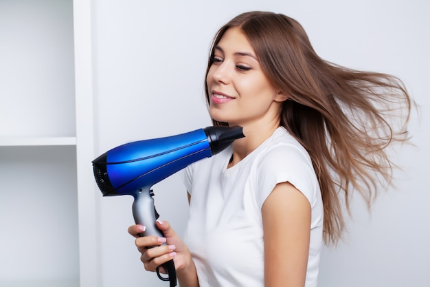 Piękna młoda modelka dba o włosy, suszy włosy za pomocą suszarki do włosów