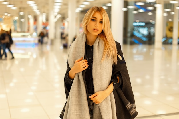 Piękna młoda modelka w modny płaszcz z szalikiem chodzenie w centrum handlowym