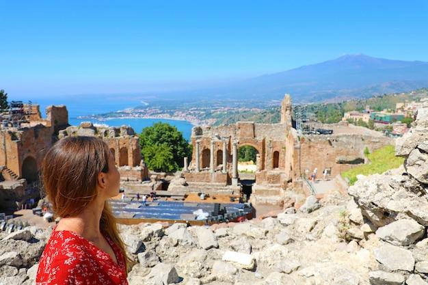 Piękna młoda modelka w ruinach starożytnego greckiego teatru w taorminie z wulkanem etna i morzem jońskim w tle, sycylia, włochy