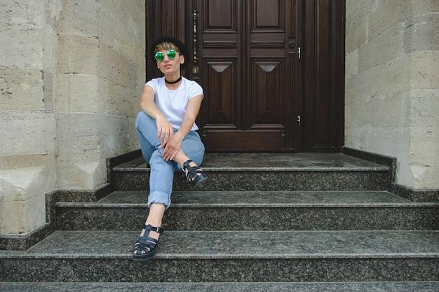 Piękna młoda modniś kobieta pozuje siedzieć na schodkach