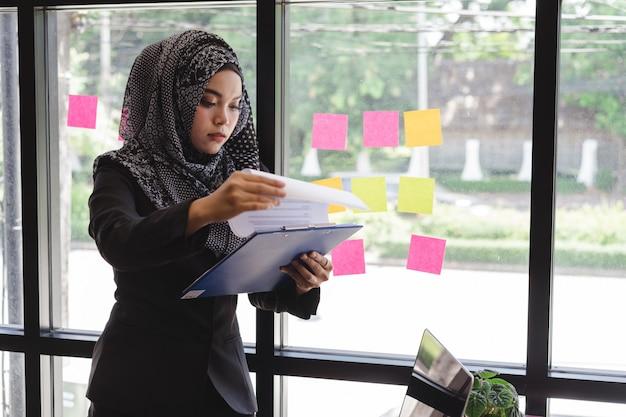 Piękna młoda muzułmańska biznesowa kobieta czyta biznesowego raportu dokument przed szklanej ściany biurem.