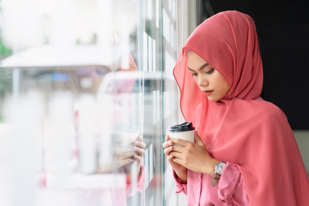 Piękna młoda muzułmańska biznesowa kobieta pije kawę przy miejscem pracy.