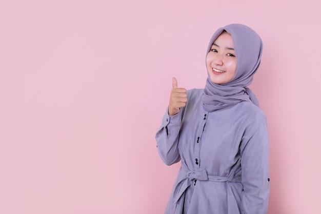 Piękna młoda muzułmańska dziewczyna robi kciuk ok znak