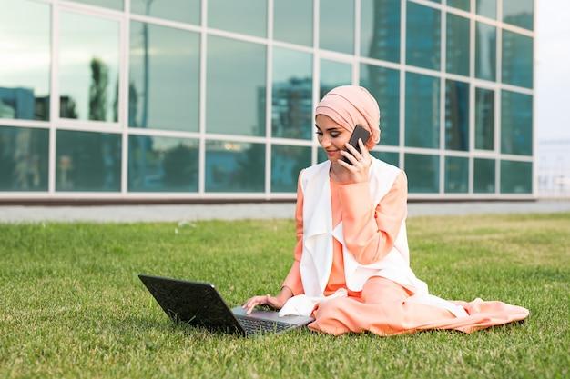 Piękna młoda muzułmańska dziewczyna siedzi z notebookiem na zewnątrz