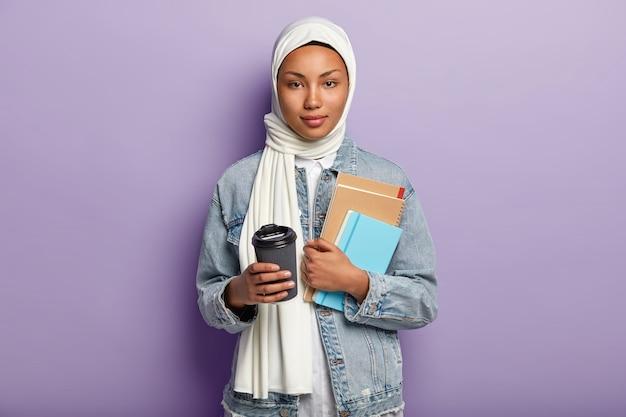 Piękna młoda muzułmańska kobieta pozuje z jej telefonem