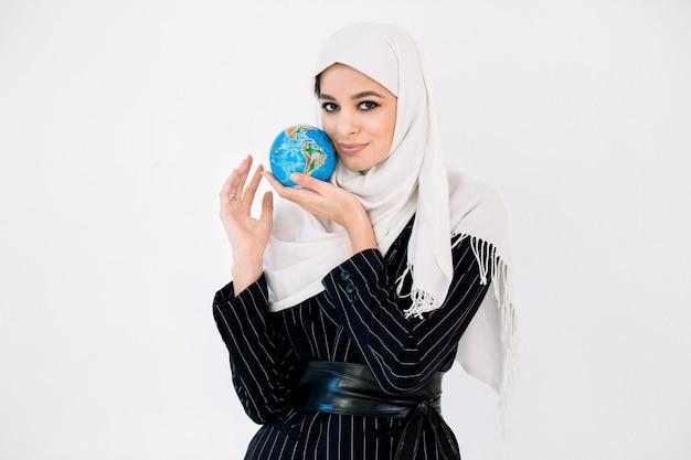 Piękna młoda muzułmańska kobieta trzyma małą planety ziemi kulę ziemską blisko jej twarzy