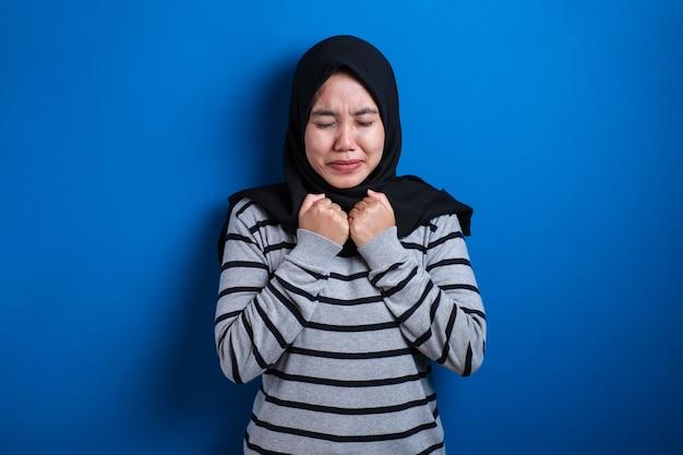 Piękna młoda muzułmańska studentka położyła rękę pod brodą. przestraszony przez coś lub kogoś obgryzającego paznokcie
