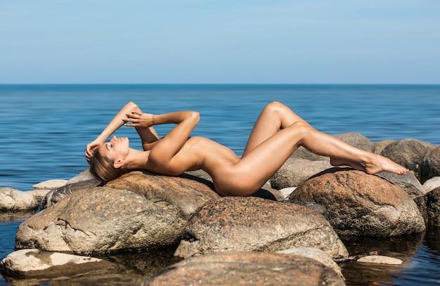 Piękna młoda naga kobieta nad morzem