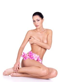 Piękna młoda naga kobieta z idealnym ciałem siedzi na białym tle