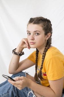 Piękna młoda nastolatka w żółtej koszuli i podarte dżinsy z plecionymi włosami sms-y przez telefon