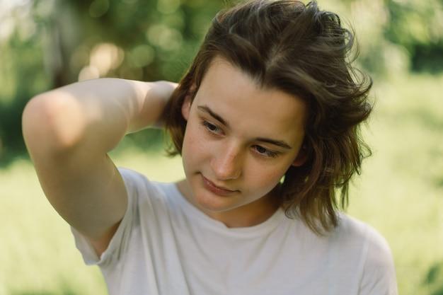 Piękna młoda nastolatka z modnymi włosami bob w białej koszulce w plenerze i patrząca na c...
