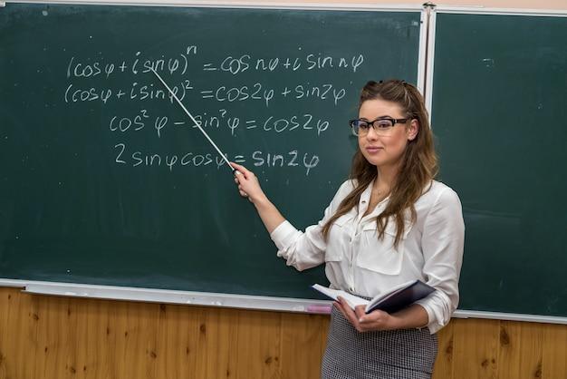 Piękna młoda nauczycielka pokazuje wskaźnik do rozwiązania ćwiczeń matematycznych w klasie. edukacja. szkoła. stanowisko.