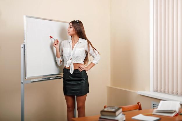 Piękna młoda nauczycielka w pobliżu tablicy na tle klas