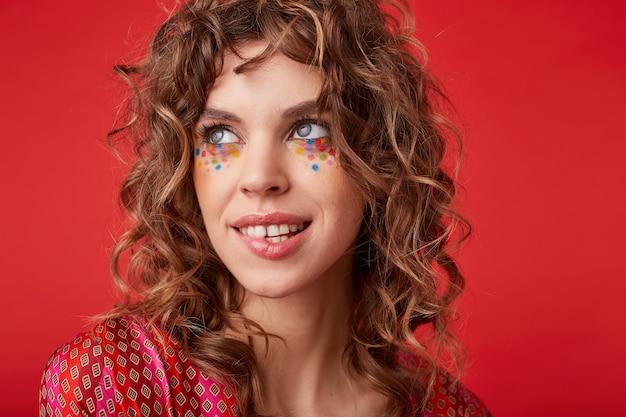 Piękna młoda niebieskooka kobieta z kręconymi włosami i świątecznym makijażem, patrząca na bok z delikatnym uśmiechem i gryzącą dolną wargą, stojąca w pstrokatym wzorzystym topie