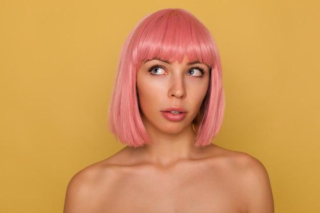 Piękna młoda niebieskooka różowowłosa kobieta z krótką modną fryzurą, patrząc w zamyśleniu w górę, stojąc nad musztardową ścianą