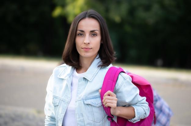 Piękna młoda nowoczesna studencka dziewczyna z plecakiem na zewnątrz